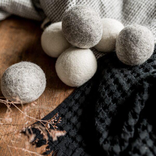 des boules de séchage de couleur grise et blanche posées sur une table en bois