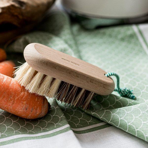 Une brosse à légumes posée sur une carotte