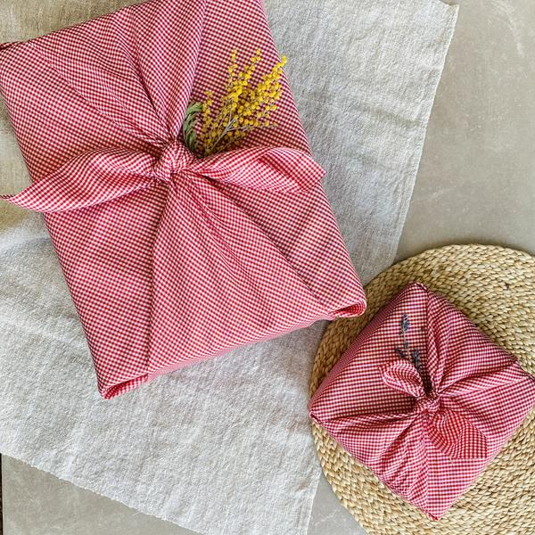 Un emballage cadeau en tissu motif vichy posé sur une une table