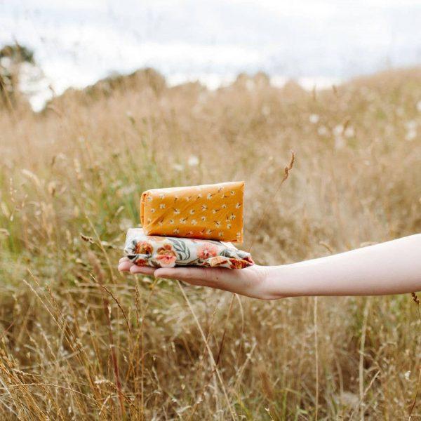 Une main qui tient des beewraps avec des coloris fleuris dans un champ