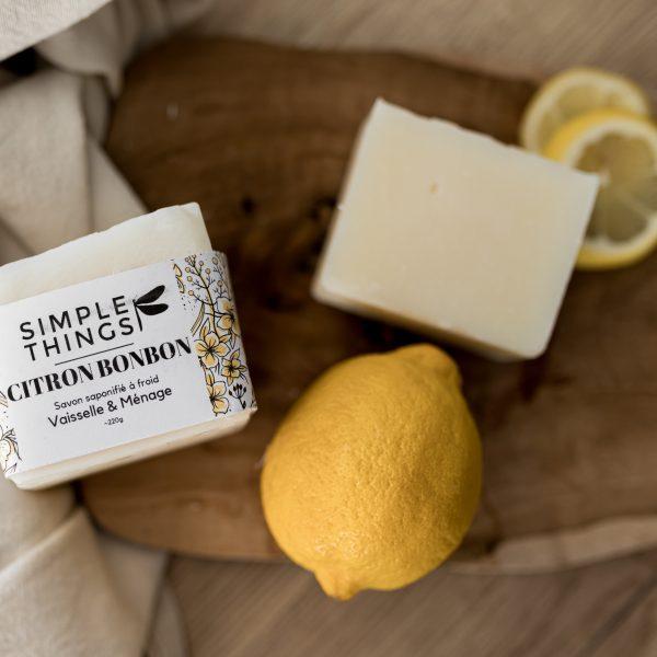 Présentation du savon ménager citron bonbon posé sur une planche à découper avec 1 citron